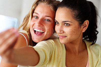 Buy stock photo Portrait of an excited young women taking picture of themselves from cellphone