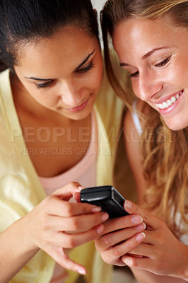 Buy stock photo Portrait of happy young women using mobile phone together