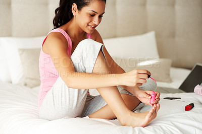 Buy stock photo Portrait of a cute young woman applying nailpaint while sitting on bed