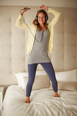 Buy stock photo Portrait of a beautiful young woman listening to music while standing on the bed at home