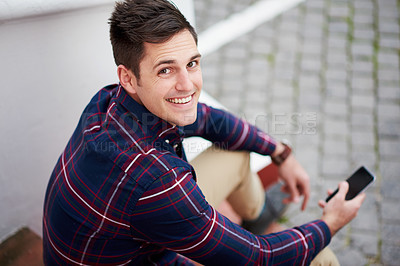 Buy stock photo High angle portrait of a handsome young man sitting on some steps outside