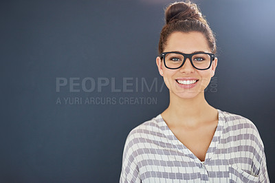 Buy stock photo Studio portrait of an attractive and happy young woman posing against a dark background