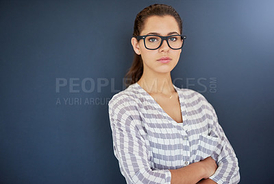 Buy stock photo Studio portrait of an attractive and serious young woman posing against a gray background