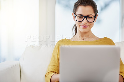 Buy stock photo Shot of an attractive young woman using her laptop while relaxing on the sofa at home
