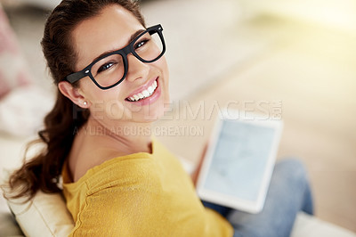 Buy stock photo High angle portrait of an attractive young woman using her tablet on the sofa at home