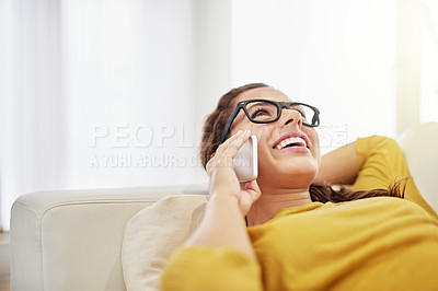 Buy stock photo Shot of an attractive young woman talking on her cellphone while relaxing on the sofa at home