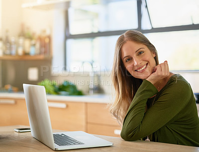 Buy stock photo Portrait of an attractive young woman using laptop on her kitchen counter at home