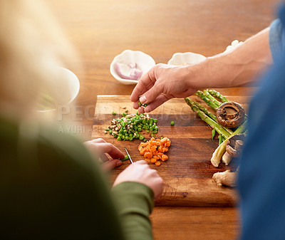 Buy stock photo Over the shoulder shot of a young couple chopping up ingredients together at their kitchen counter for dinner