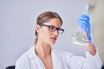 Buy stock photo Shot of a scientist examining a beaker of liquid while standing in a laboratory
