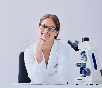 Buy stock photo Portrait of a smiling scientist sitting next to a microscope at a desk in a laboratory