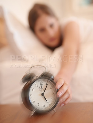 Buy stock photo Cropped shot of a young woman waking up and reaching for her alarm clock at home