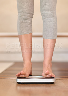 Buy stock photo Closeup shot of a young woman weighing herself on a scale at home