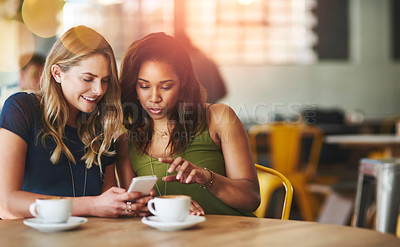 Buy stock photo Cropped shot of girlfriends sharing something on a cellphone while sitting in a cafe