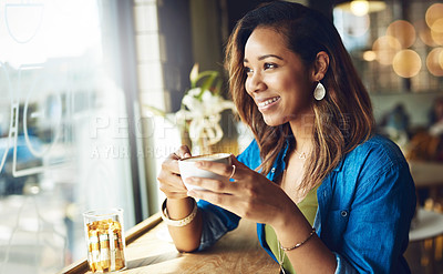 Buy stock photo Cropped shot of an attractive young woman enjoying a cup of coffee in a cafe