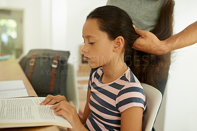 Buy stock photo Shot of a young girl reading a book while her father brush her hair
