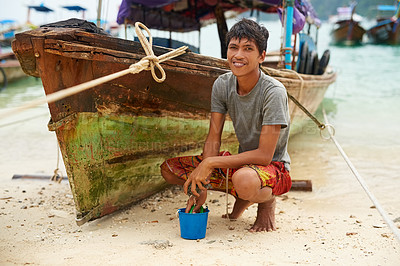 Buy stock photo Portrait of a man from Thailand next to his boat at the water's edge