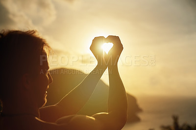 Buy stock photo Shot of a young man making a heart shape with his hands around the sun while on holiday