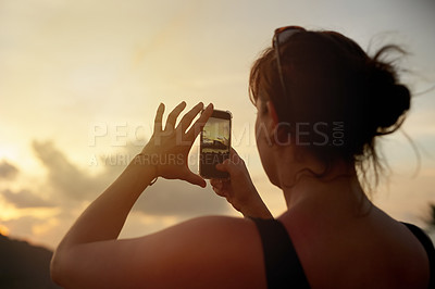 Buy stock photo Shot of a young woman photographing a tropical view with her cellphone while on holiday