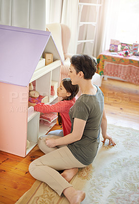 Buy stock photo Shot of a young mother and her daughter playing with a dollhouse
