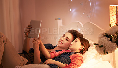 Buy stock photo Cropped shot of a young mother reading a bedtime story to her daughter