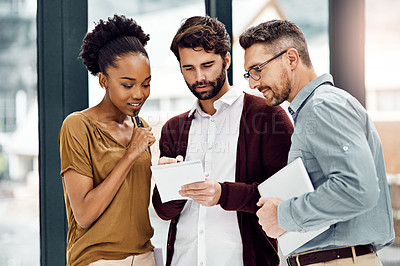 Buy stock photo Cropped shot of three businesspeople looking at a digital tablet in their office