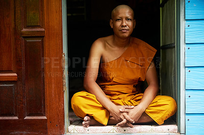 Buy stock photo Portrait of a buddhist monk sitting in the doorway of his home