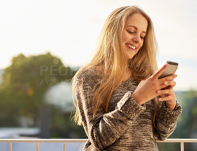 Buy stock photo Cropped shot of an attractive young woman texting on her cellphone outside