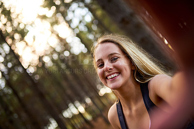 Buy stock photo Portrait of a happy young woman taking a selfie while exploring a forest on her own