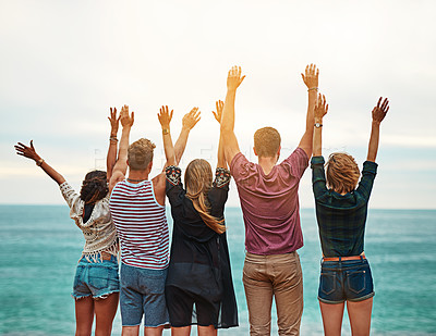 Buy stock photo Rear view shot of a group of friends standing with their arms outstretched outside