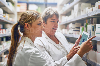 Buy stock photo Shot of two pharmacists using a digital tablet while checking stock on the shelf