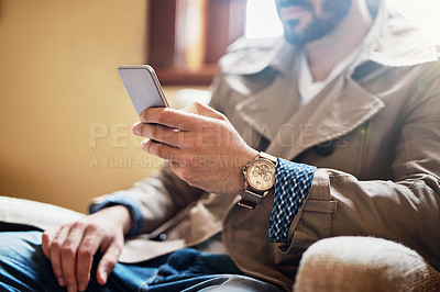 Buy stock photo Cropped closeup shot of an unrecognizable young man sitting in a chair using a cellphone