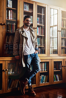 Buy stock photo Portrait of a handsome and stylish young man leaning against a bookcase at home