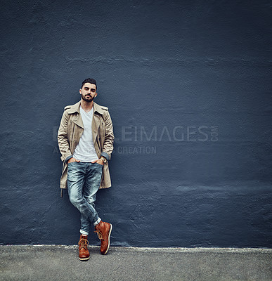 Buy stock photo Portrait of a fashionable young man wearing urban wear and posing against a gray wall