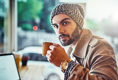 Buy stock photo Portrait of a handsome young man sitting at a cafe counter using a laptop and drinking a cup of coffee