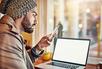 Buy stock photo Shot of a stylish young man reading a text message and using a laptop while sitting in a cafe