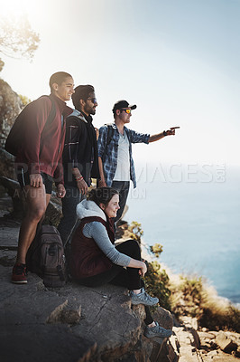 Buy stock photo Shot of a young man pointing something out to his friends while on a mountain hike
