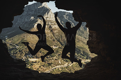 Buy stock photo Rearview shot of a young couple jumping in excitement while hiking in the mountains