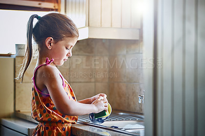Buy stock photo Cropped shot of a little girl washing dishes at home