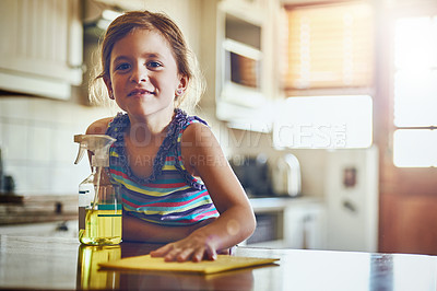 Buy stock photo Portrait of a little girl cleaning a kitchen surface at home