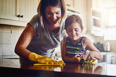 Buy stock photo Cropped shot of a mother and her little daughter cleaning a kitchen surface together at home