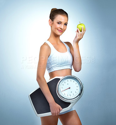 Buy stock photo Portrait of a health-conscious young woman posing with an apple and a scale in studio