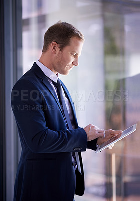 Buy stock photo Shot of a businessman using a digital tablet at work