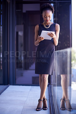Buy stock photo Shot of a young businesswoman using a digital tablet at work