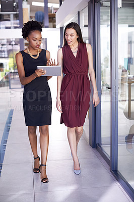 Buy stock photo Shot of two businesswomen working together on a digital tablet in an office
