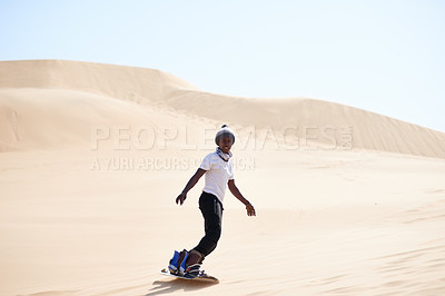 Buy stock photo Portrait of a young man sandboarding in the desert