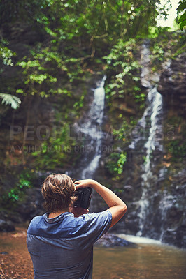 Buy stock photo Rearview shot of a young photographer taking a picture of a waterfall in the jungle