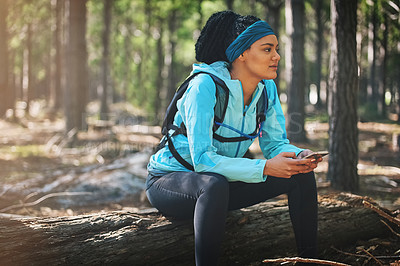 Buy stock photo Cropped shot of an athletic young woman sending a text while jogging in the woods