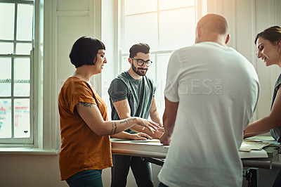 Buy stock photo Cropped shot of a group of young designers working around a drafting table