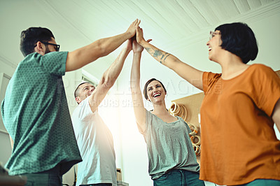 Buy stock photo Cropped shot of a group of young designers high-fiving in the office