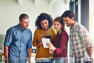 Buy stock photo Cropped shot of a team of designers working together on a digital tablet in an office